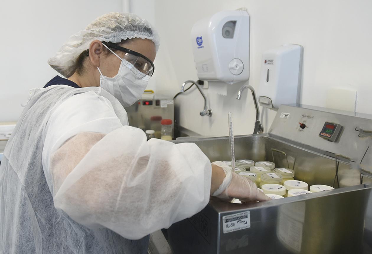 Mulher com touca, avental, máscara, luva e óculos cirúrgicos manipula vidros com tampa em recipiente metálico