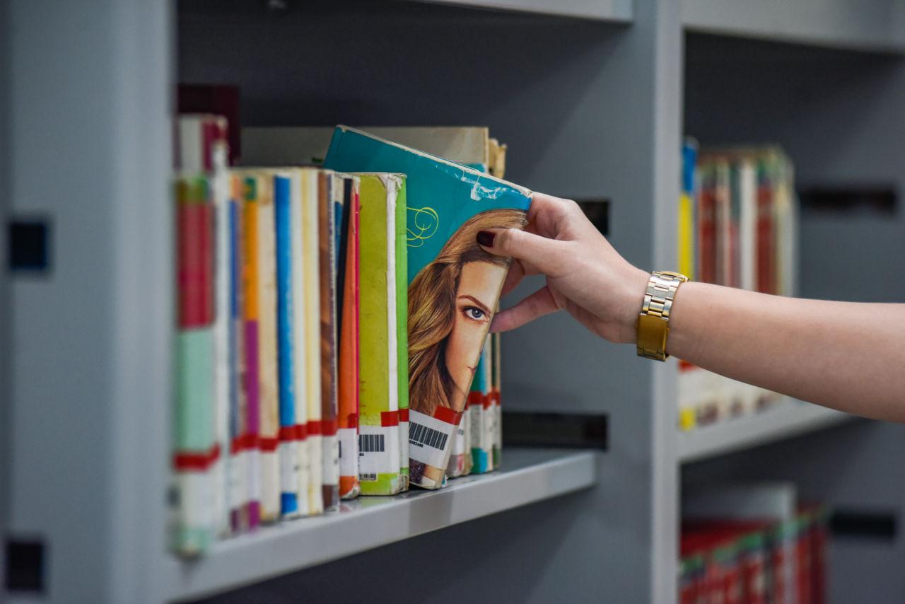 Imagem mostra mão de mulher pegando livro em estante
