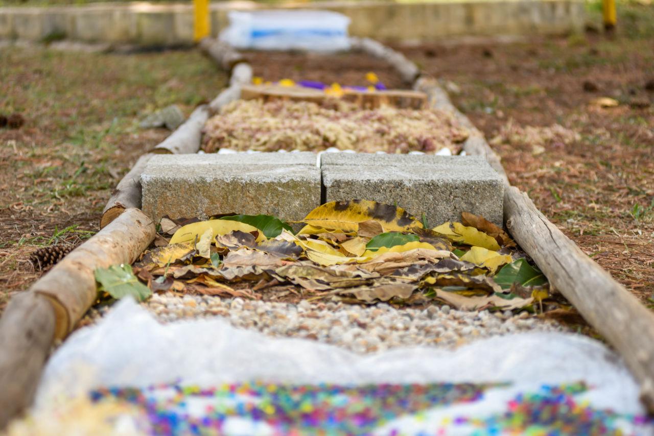 imagem mostra caminho com diferentes tipos de materiais em cada espaço, há bolinhas coloridas, pequenas pedras, folhas secas, bloco de concreto.