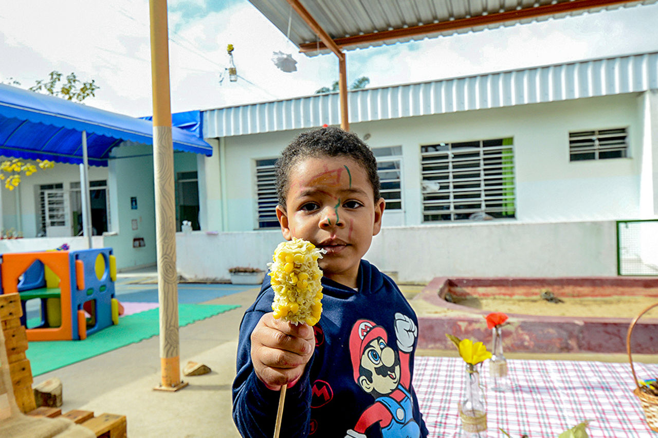 imagem mostra aluno com blusa azul, segurando palito com milho cozido. Ele está com o rostinho com riscos coloridos.
