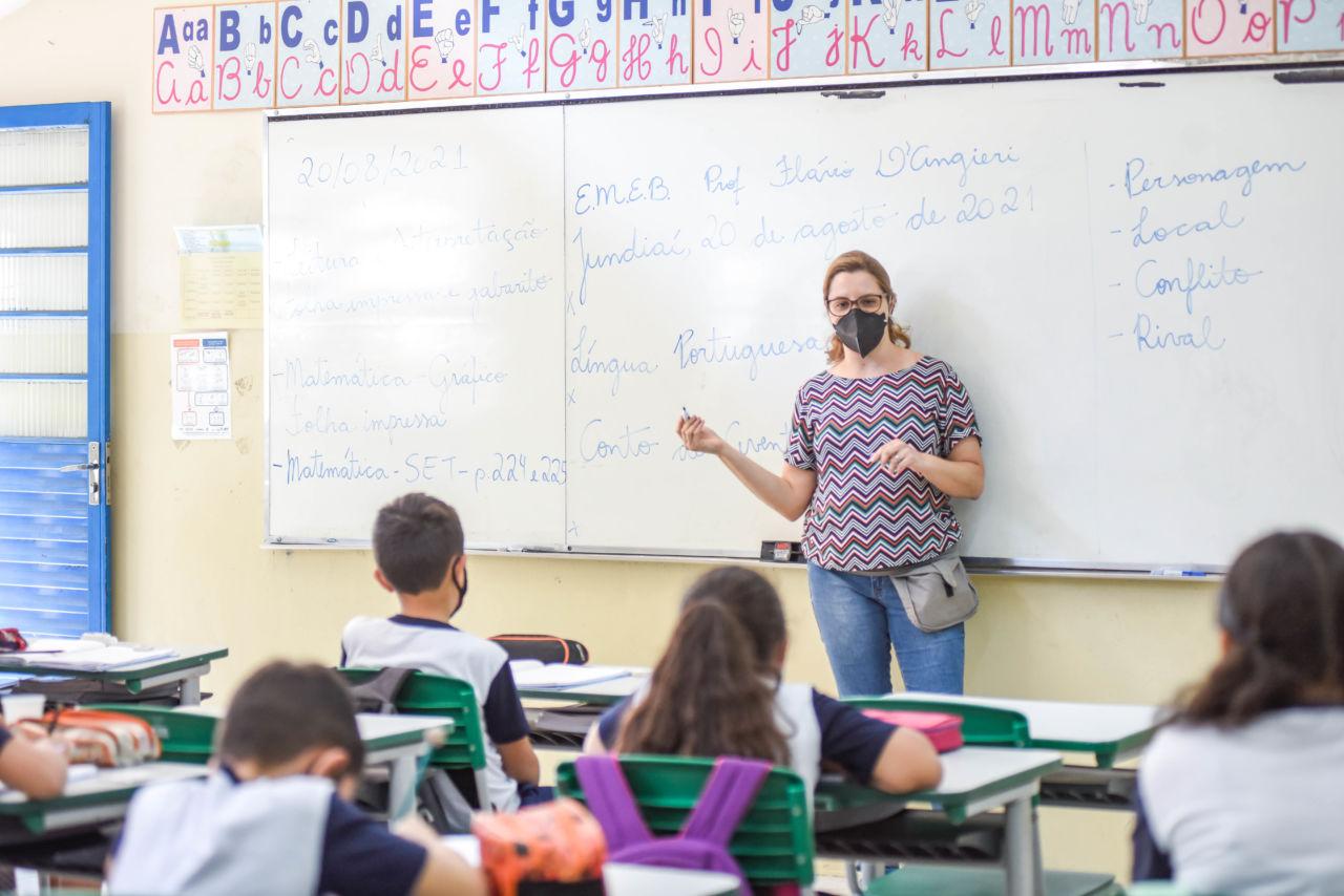 mulher (professora) está em frente ao quadro branco onde há várias anotações em azul