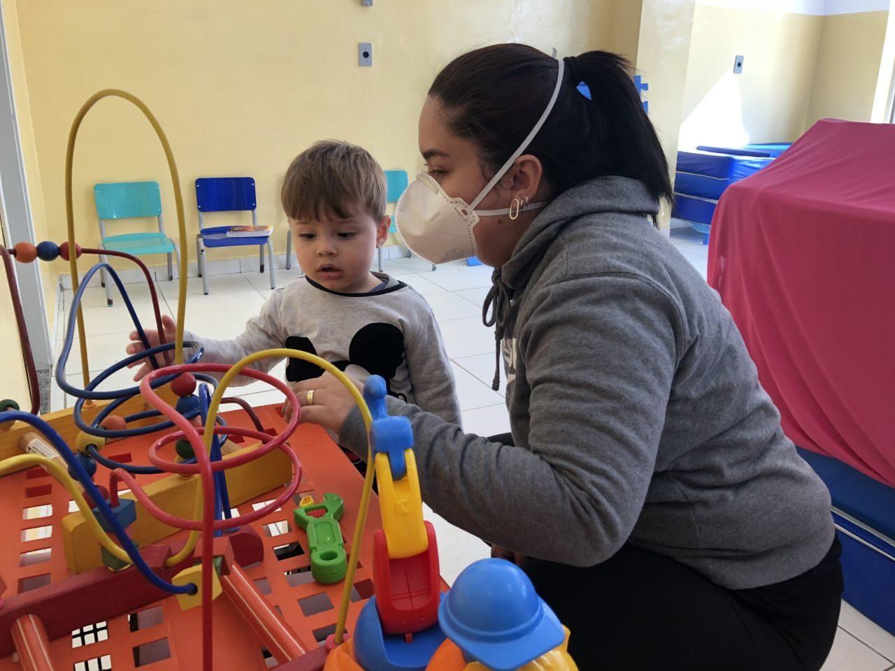 Mulher de cabelo comprido e preso, usando máscara, interage com menino pequeno enquanto ele olha para brinquedo com cabos e bolas de madeira