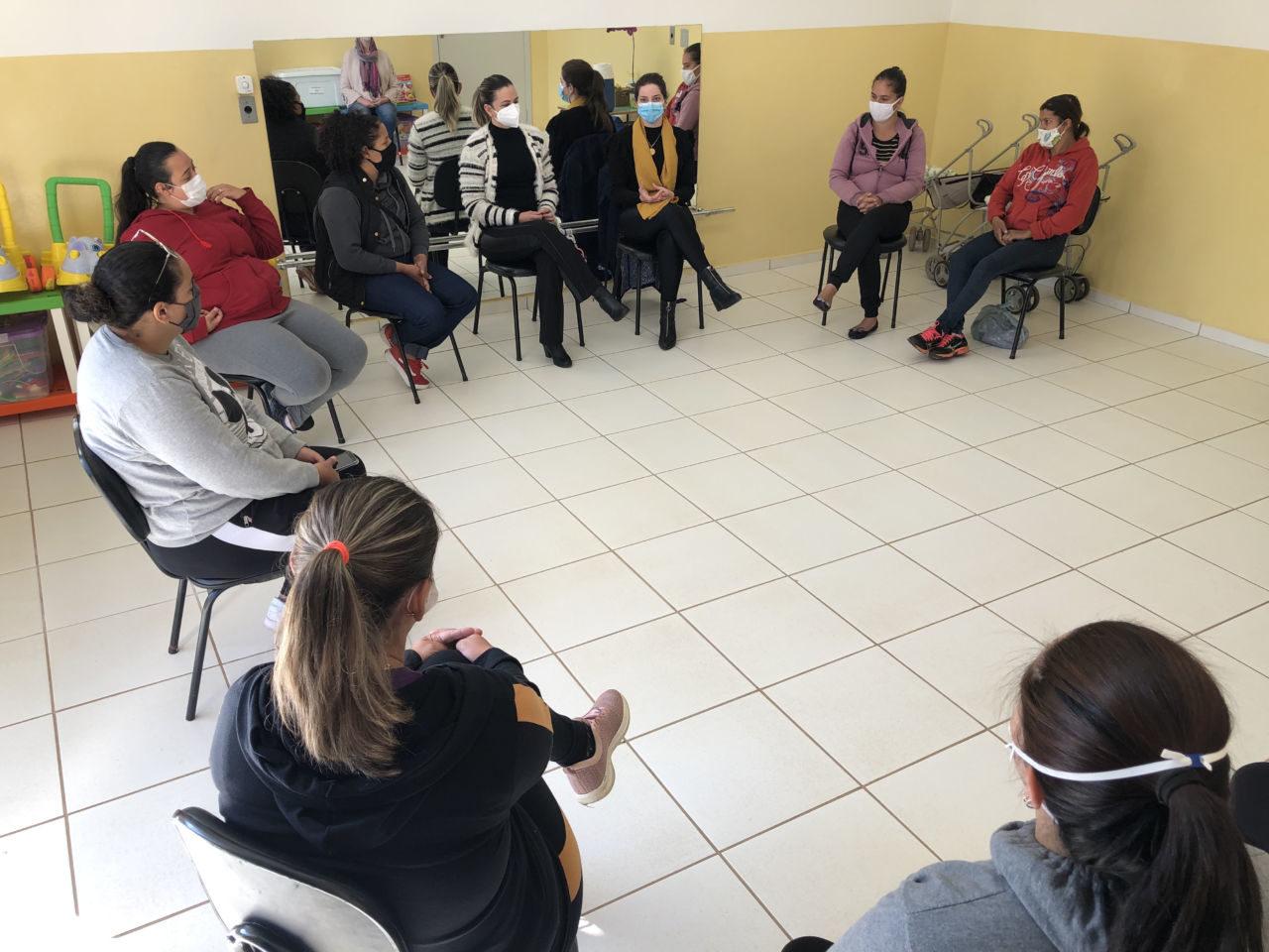 Mulheres usando máscaras e sentadas em semicírculo conversando, com um espelho horizontal ao fundo da sala