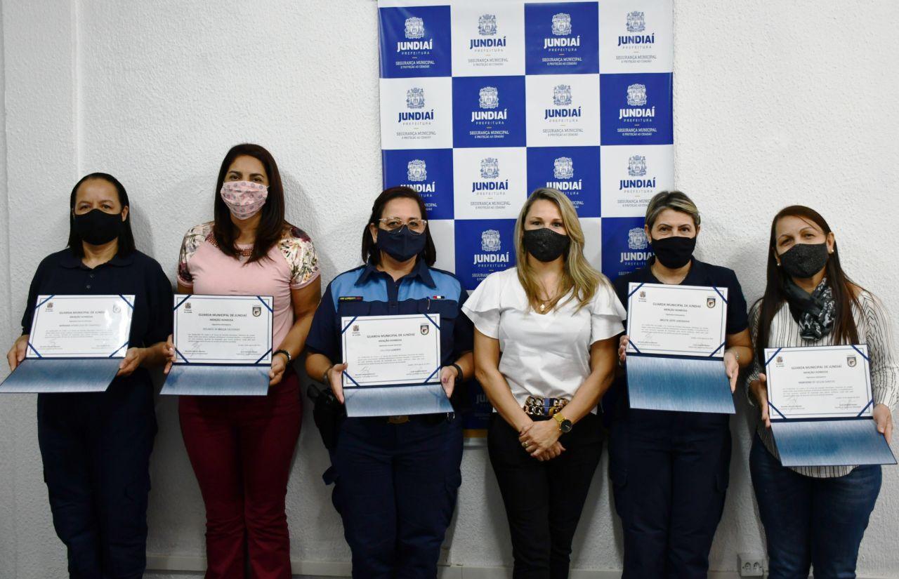 Seis mulheres com máscaras, algumas com uniformes policias, em foto posada em frente a uma parede com mosaico com símbolos