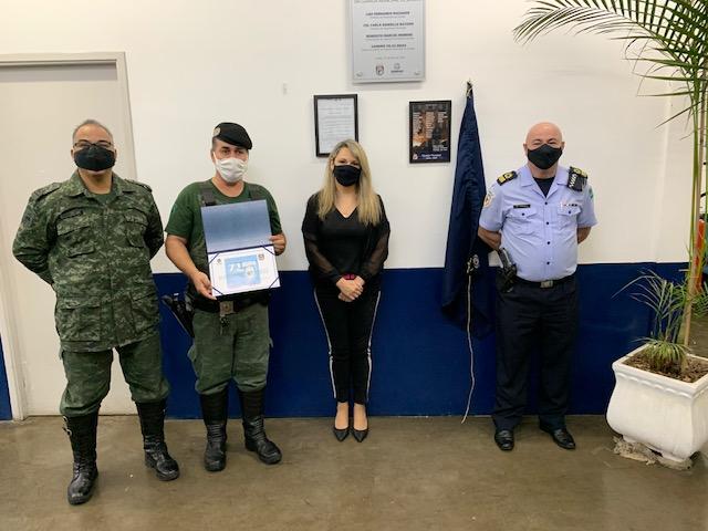 Foto posada de três homens com uniformes de guardas e uma mulher, todos com máscara, em frente a uma parede onde se vê placa recém-descerrada