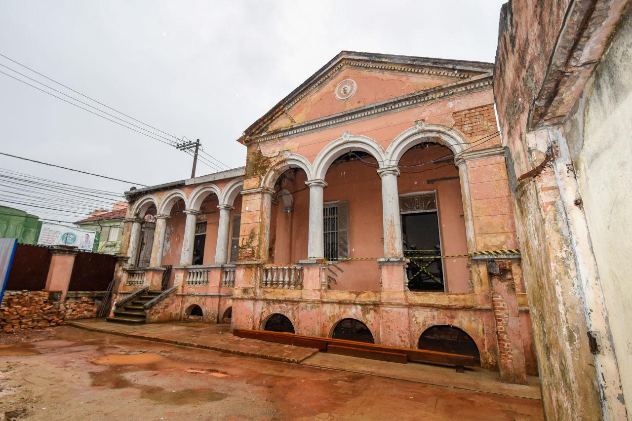 Construção antiga, com paredes rosas, a tinta está descascando