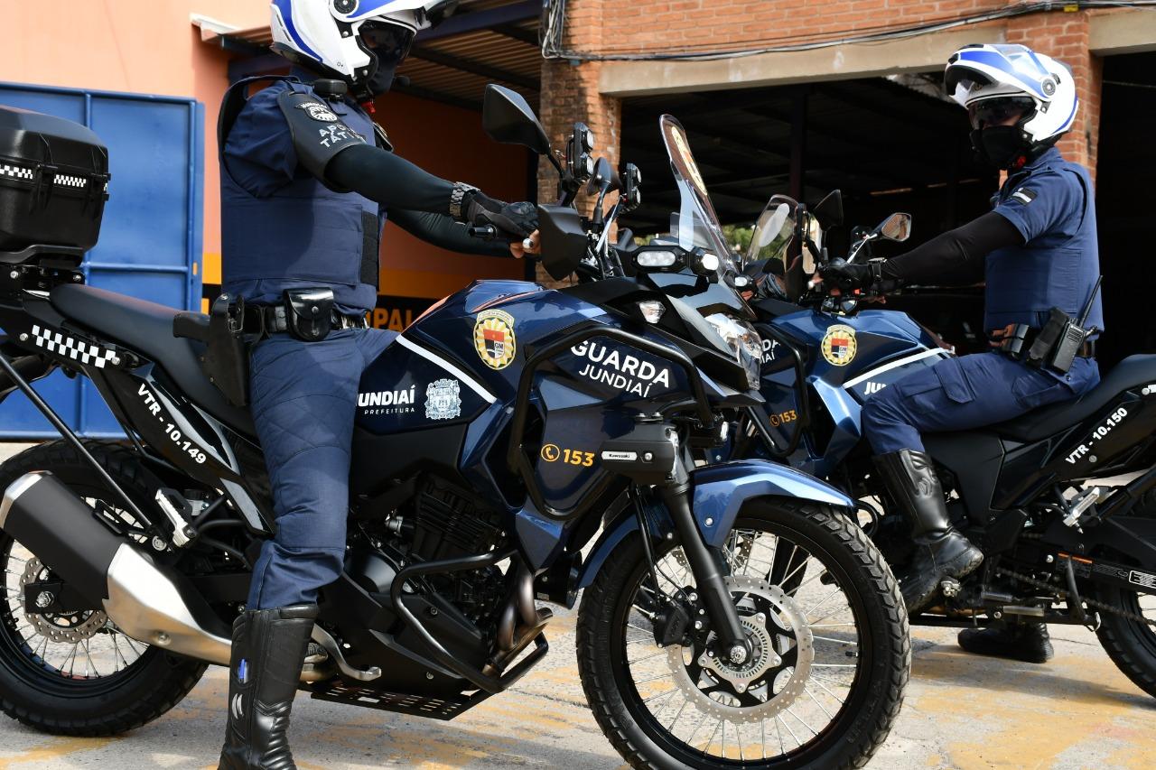 Dois homens com uniformes policiais com máscaras e capacetes sobre motos com identidade visual da corporação policial