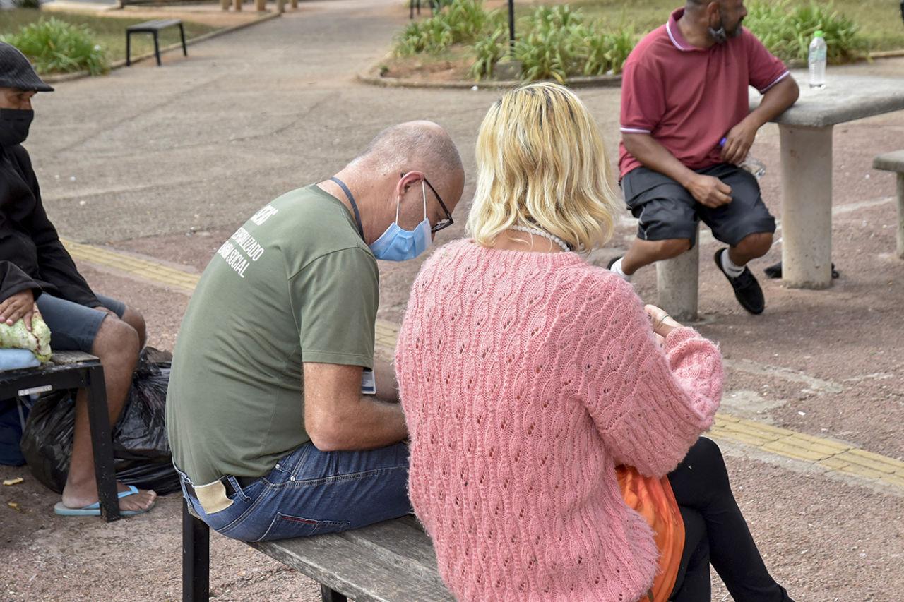 Homem de máscara e óculos, sentado em banco de praça, na posição lateral com pessoa de costas com suéter rosa e cabelos loiros na altura do pescoço, com as pernas cruzadas e colar de bolinhas e pernas cruzadas