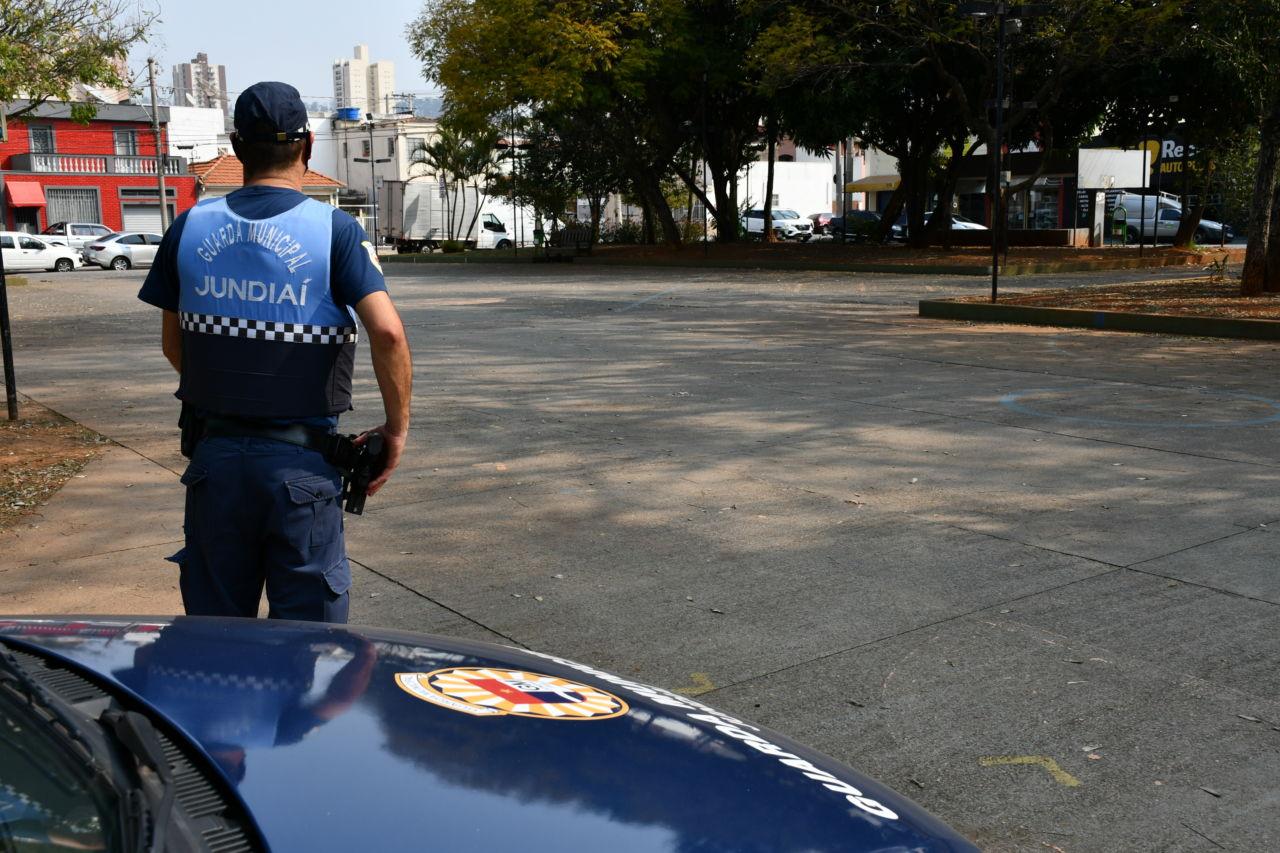 Homem de farda policial de costas, segurando revólver com a mão direita na cintura, em frente a uma viatura policial, e olhando para praça com pavimento de concreto, árvores e residências ao fundo