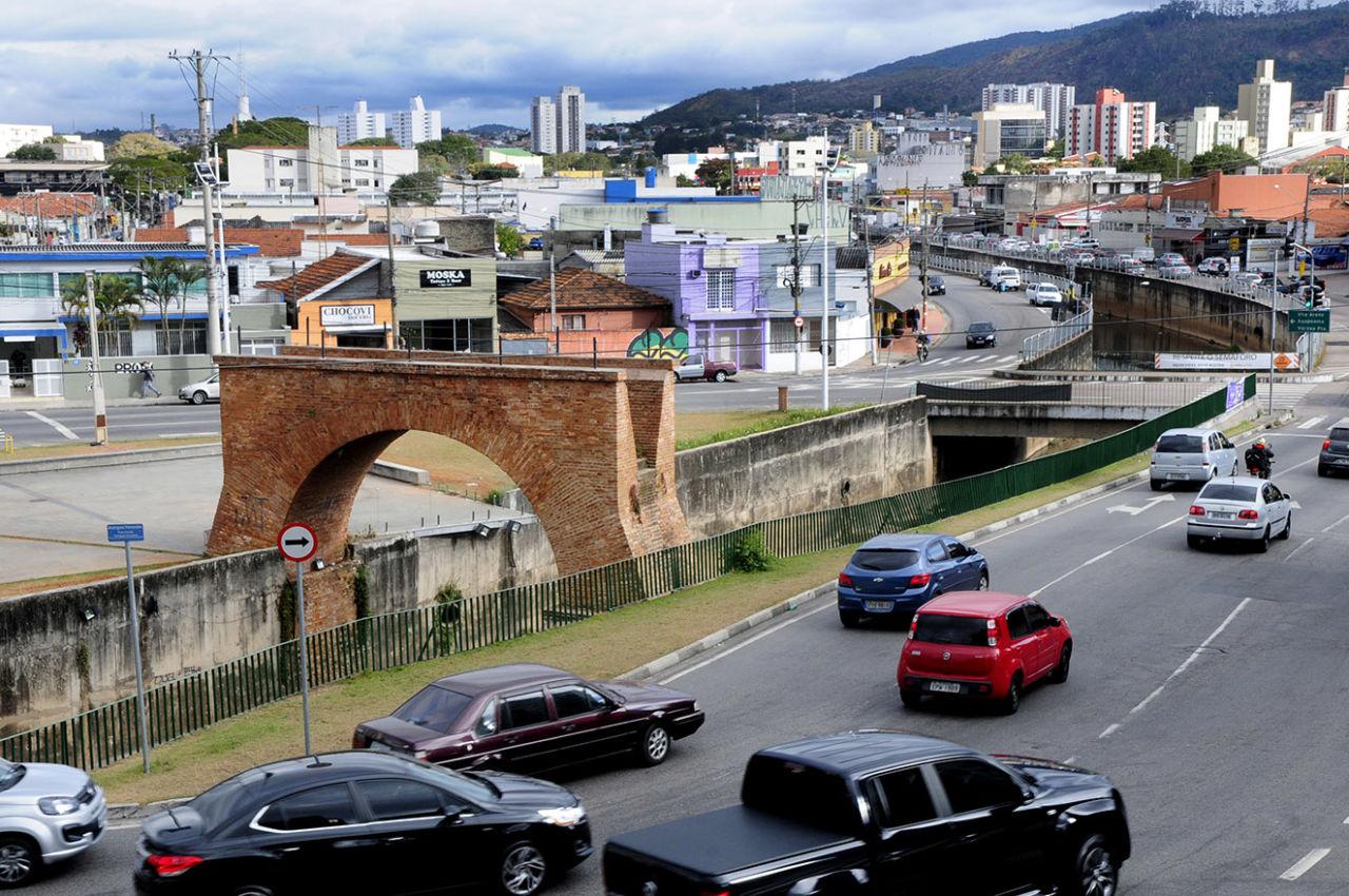 Vista do alto de ambiente urbano, com casas e prédios, e veículos de diversos formatos e tamanhos transitando em via às margens de rio com pontes de tijolos à vista