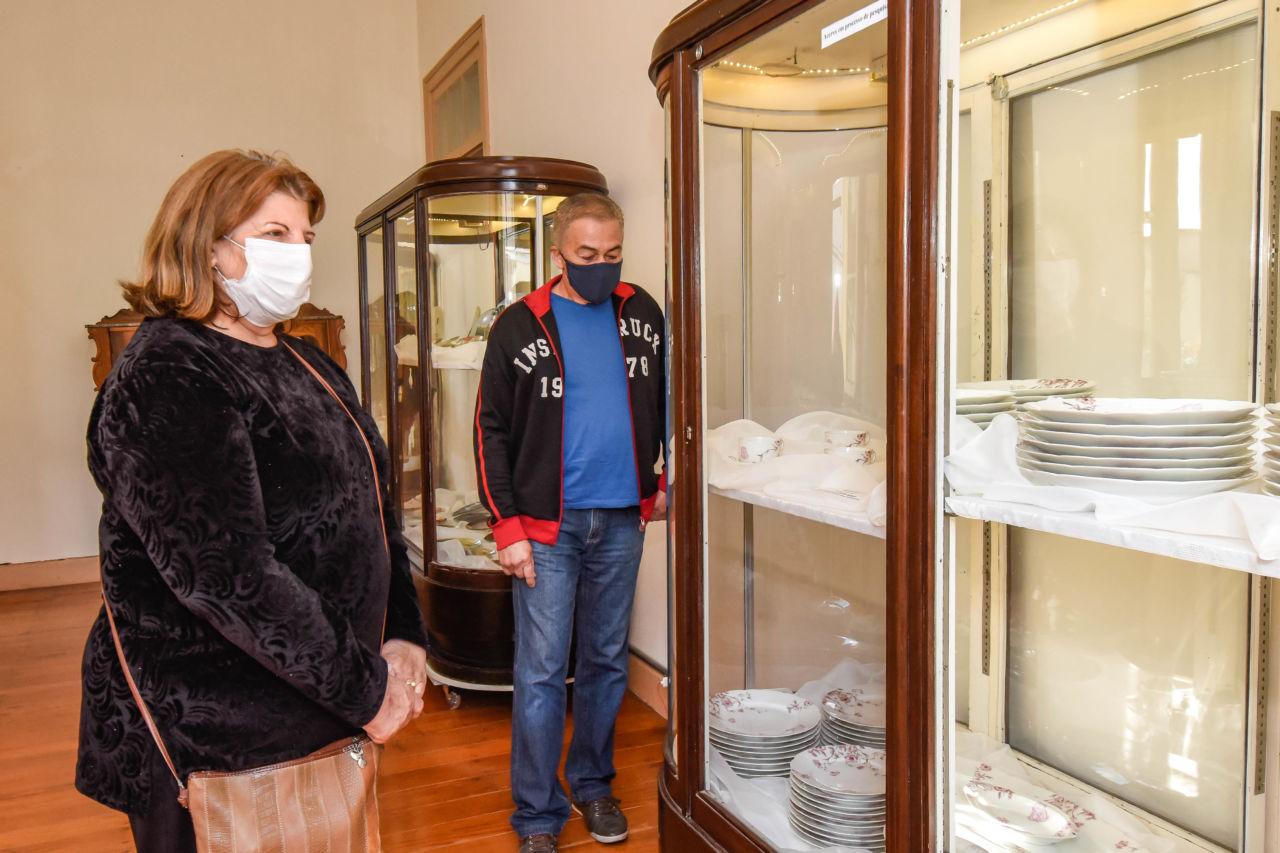 Homem e mulher com máscaras olhando para vitrine com pratos empilhados