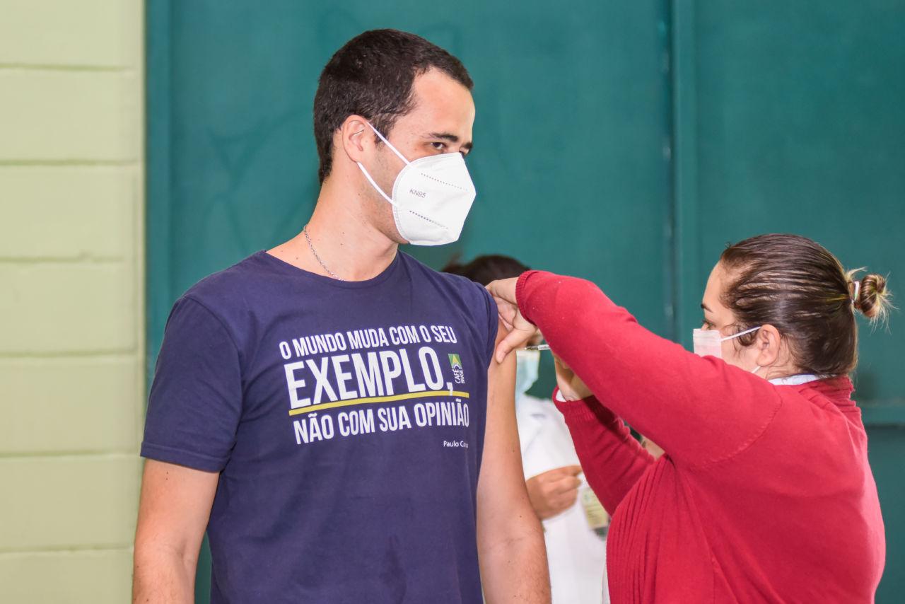 Mulher com blusa rosa, aplica vacina no braço de um homem, moreno, com camiseta onde se lê a frase: O mundo muda com o seu exemplo, não com sua opinião.