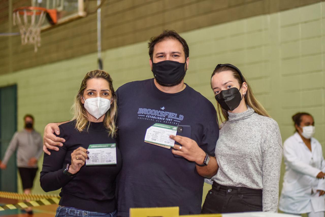 Mulher loira, homem moreno e garota loira. Mulher e homem seguram a carteirinha de vacinação contra a covid-19.