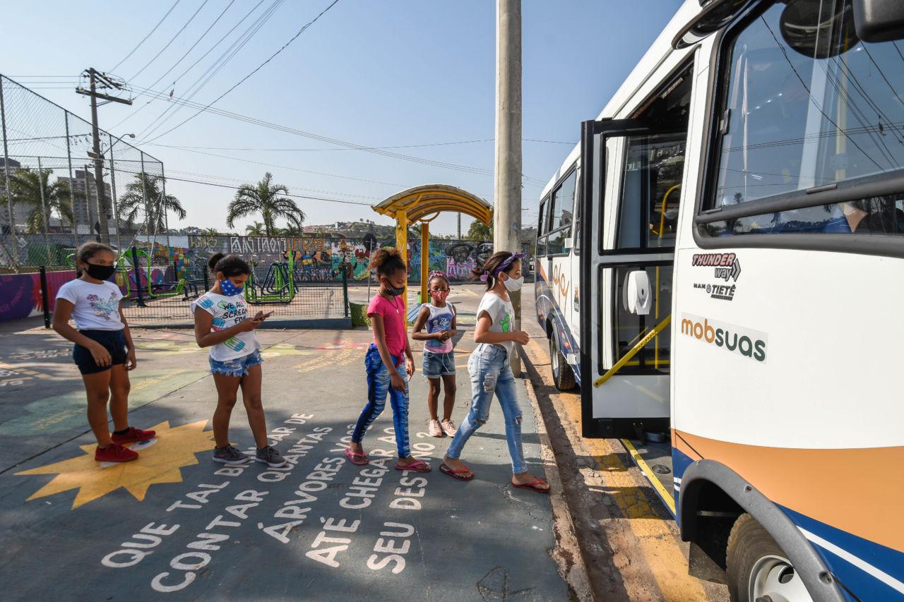 Cinco meninas com máscaras em fila para subir em ônibus estacionado em ponto de ônibus de praça com pinturas coloridas no chão