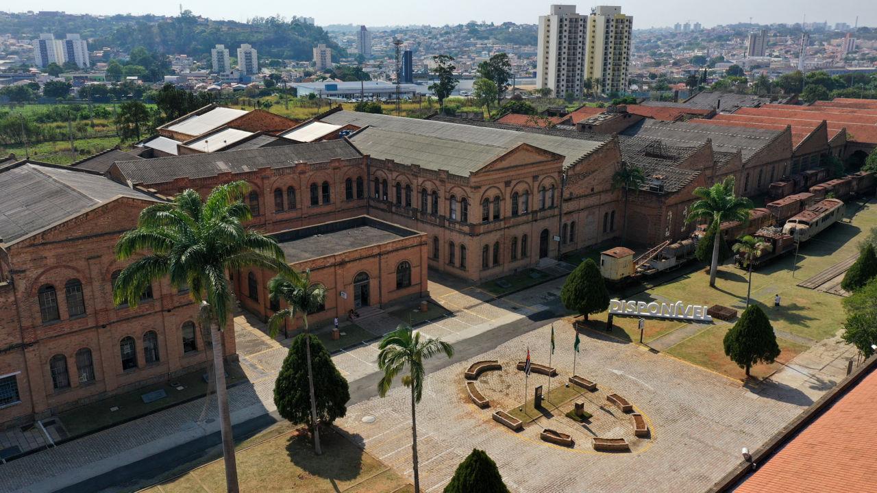 Foto aérea de prédio histórico em estilo inglês com tijolos à vista, com extensa área de jardim, palmeiras e locomotivas férreas, com prédios da cidade ao fundo