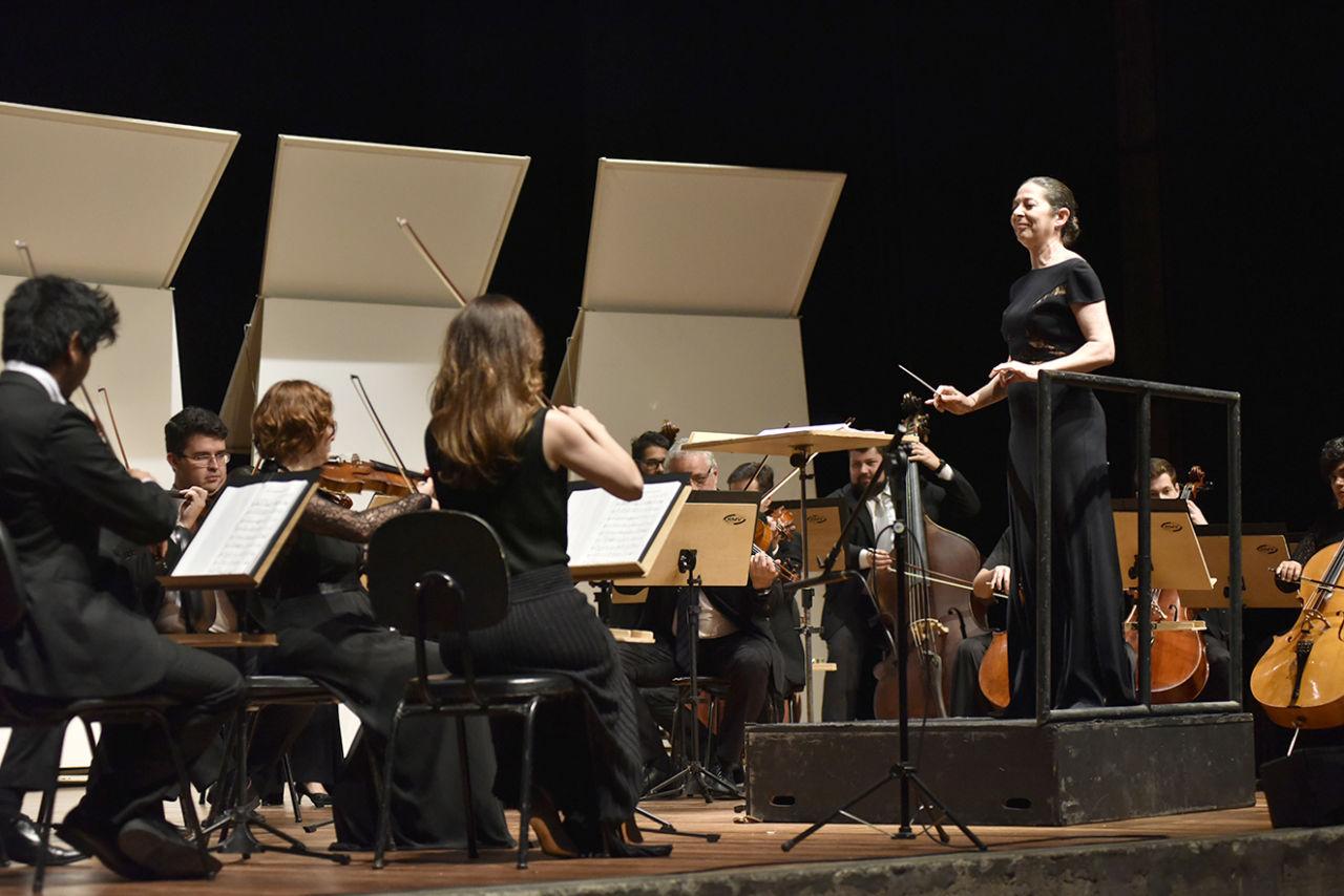 Palco de teatro com composição de músicos de orquestra sentados, com mulher de vestido longo e cabelo preso em pé, sobre tablado com barras laterais para as mãos