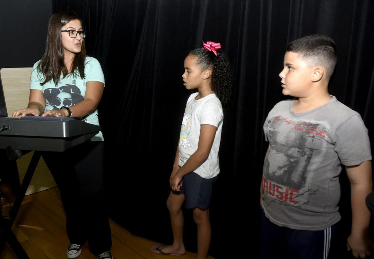 Mulher em pé usando óculos toca teclado e interage com uma menina e um menino, também em pé