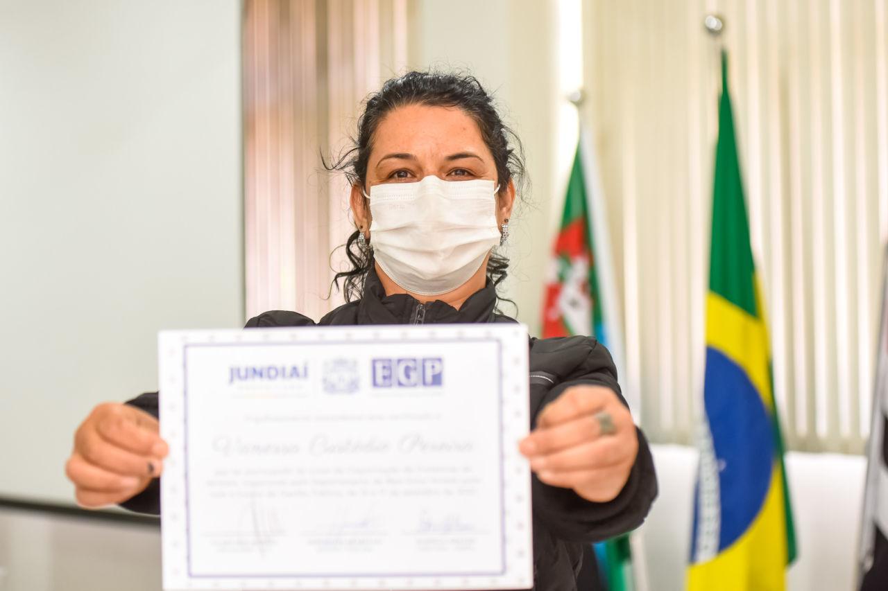 Mulher morena, com máscara branca, segura nas mãos um certificado, branco, com logos na parte superior em azul