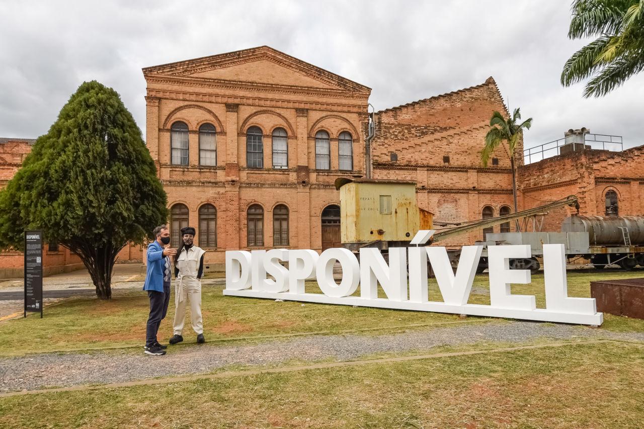 """Um homem e uma mulher usando máscaras conversam em frente a um letreiro onde se lê """"DISPONÍVEL"""", em um gramado, com prédio histórico de tijolos à vista ao fundo"""
