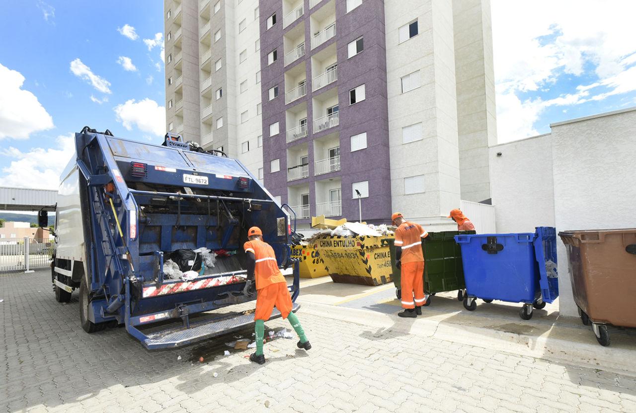 Homens de uniforme no entorno de caminhão, caçambas e contêineres de lixo, com prédio alto ao fundo