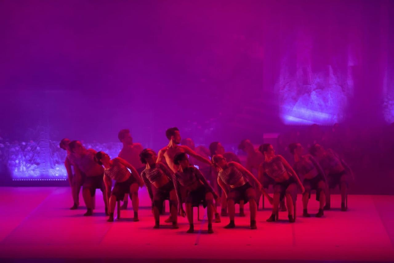 Performance de dança, com bailarinos perfilados sobre palco, agachados sobre os joelhos, e com as cabeças olhando para o lado