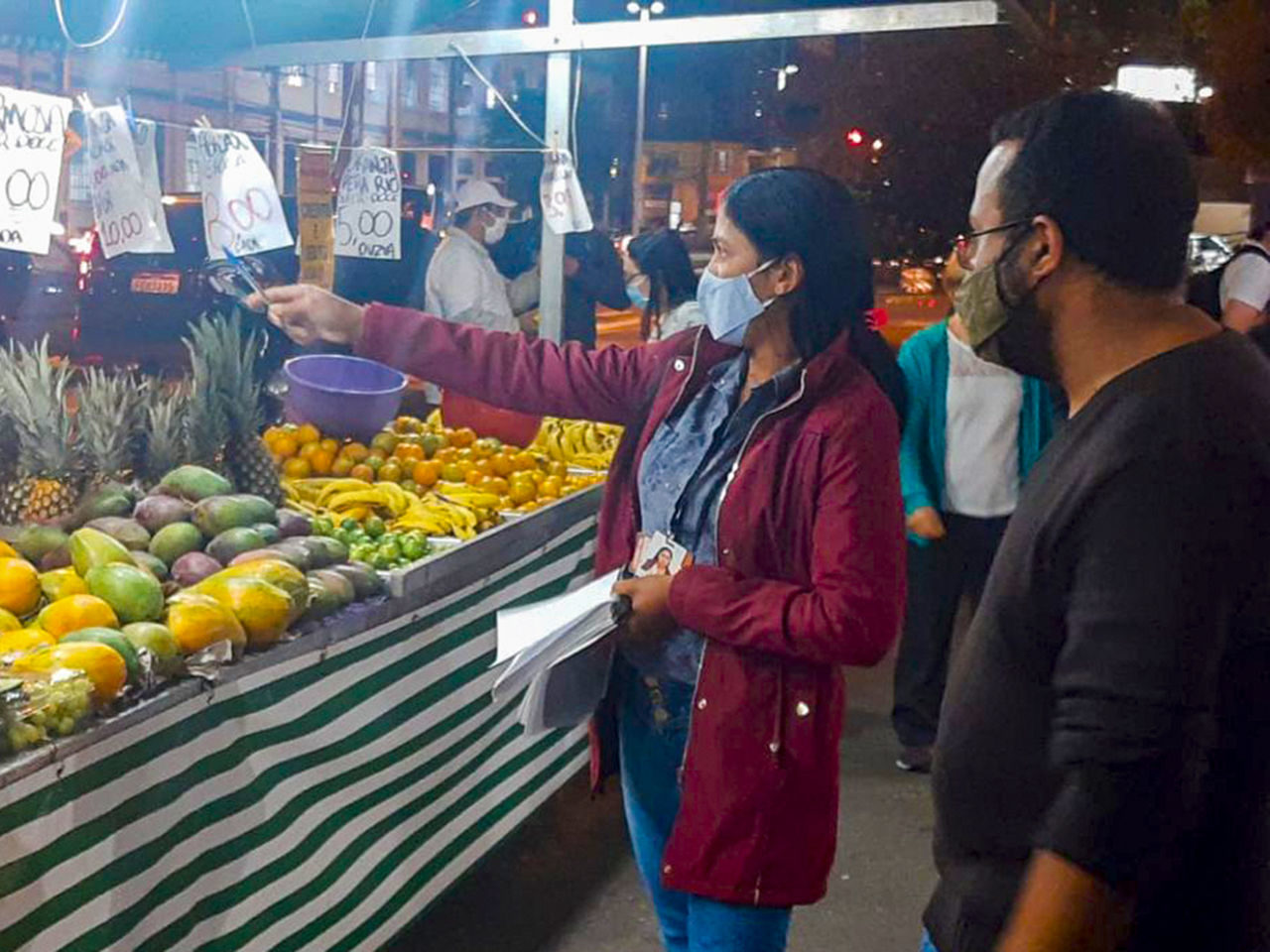 Foto é em feira, em frente a uma barraca de frutas, mulher está com caderno em uma das mãos e caneta na outra, com a qual aponta para placa com preços.