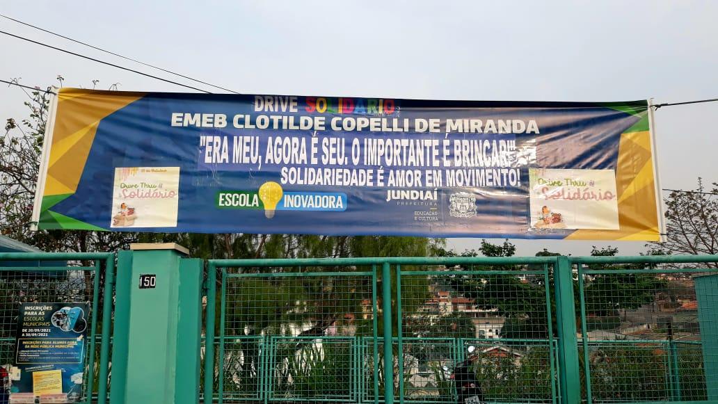 Faixa em frente à escola convida para o Drive-thru solidário da EMEB Clotilde Copelli de Miranda