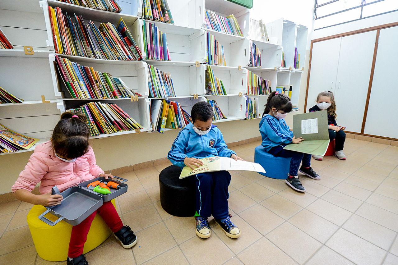 Três meninas e um menino usando máscaras, alguns com uniformes escolares, sentados em poltronas e folheando livros em frente a prateleiras