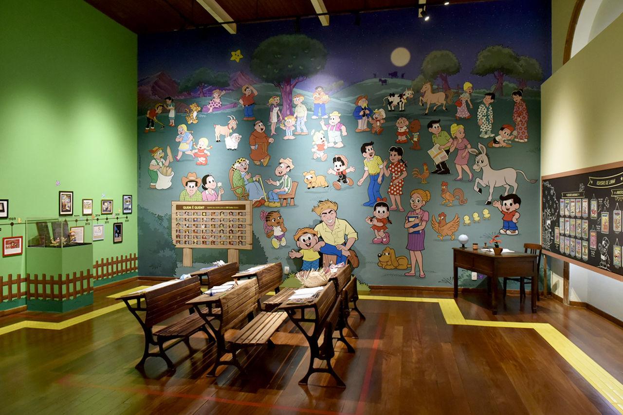 Sala de exposição com carteiras de madeira simulando sala de aula e personagens infantis na parede de fundo