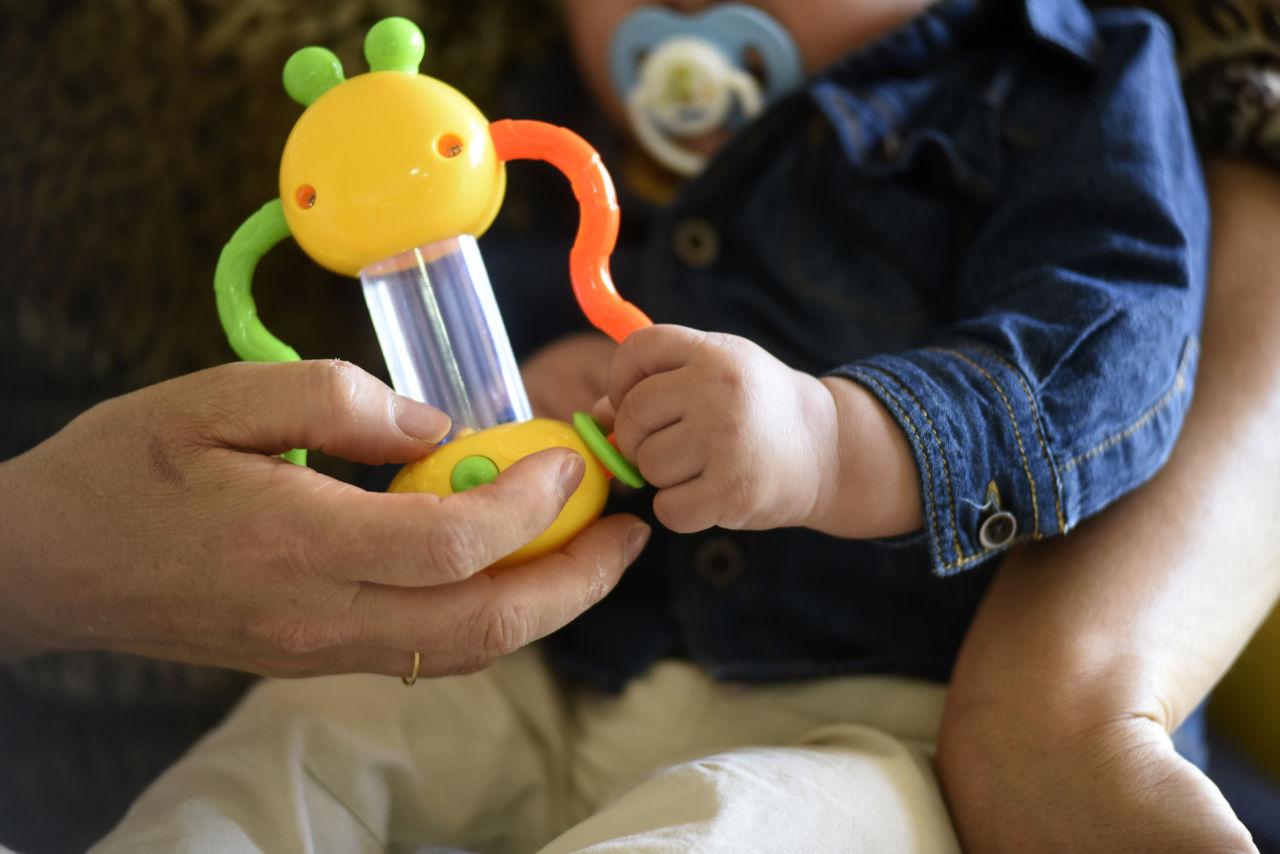 Detalhe de mão de mulher adulta, com aliança no dedo, segurando um brinquedo infantil, com uma criança de colo, usando chupeta