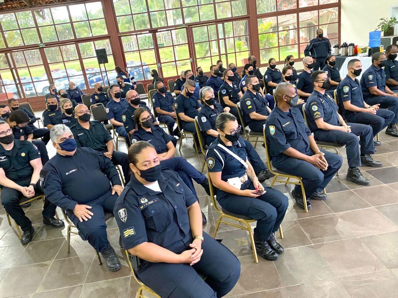 Homens e mulheres com máscaras e uniformes policiais sentados em fileiras de cadeiras em salão amplo, com portas e janelas de vidro ao fundo