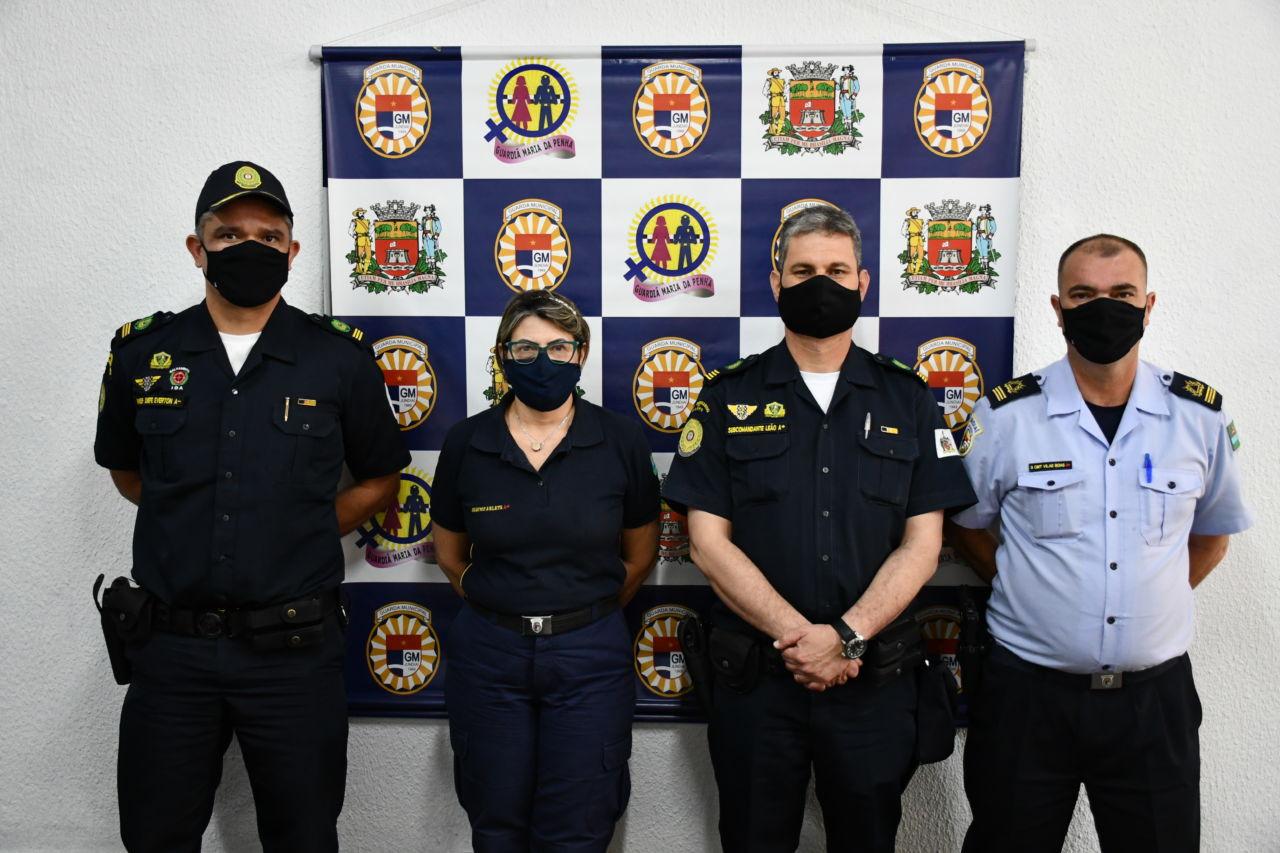 Três homens e uma mulher, com uniformes de policiais e usando máscaras, em frente a um muro com banner com mosaico de brasões