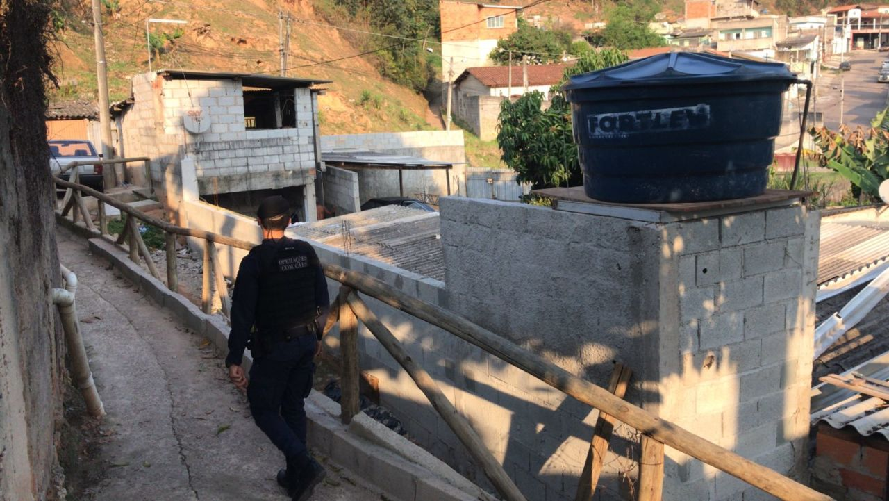 Homem com uniforme policial anda de costas por corredor, entre casas de blocos e uma caixa d'água redonda, com mais casas ao fundo