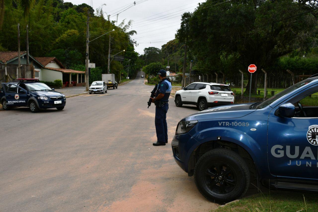 Viaturas policiais posicionadas de atravessado em via asfaltada e com arborização, com mais carros estacionados, e homem com roupa de policial segurando uma arma