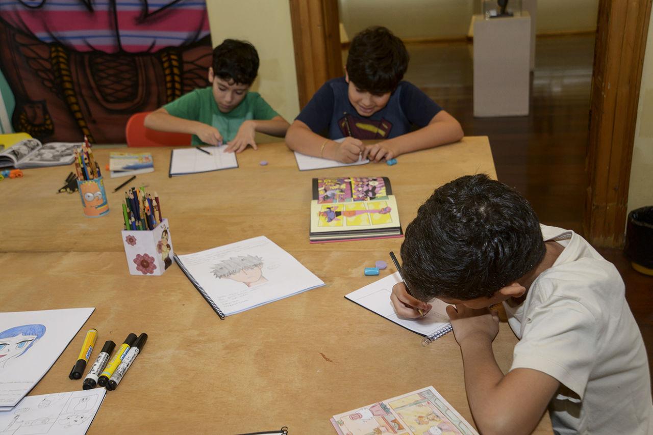 Três garotos, sentados ao redor de uma mesa quadrada de madeira, fazendo desenhos em caderno, com livros e lápis sobre a mesa