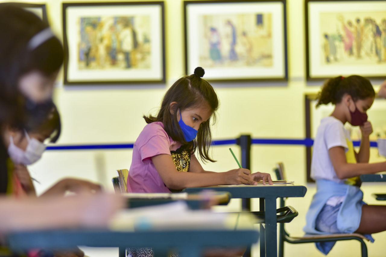 Crianças usando máscaras, sentadas em carteiras escolares, realizando atividade com lápis e papeis