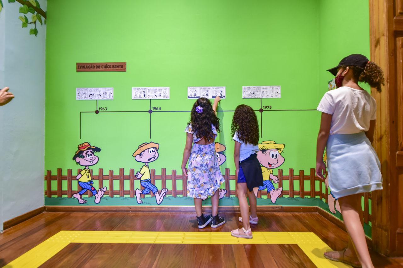Três meninas de costas apontam para parede com desenhos em diversas versões do personagem Chico Bento