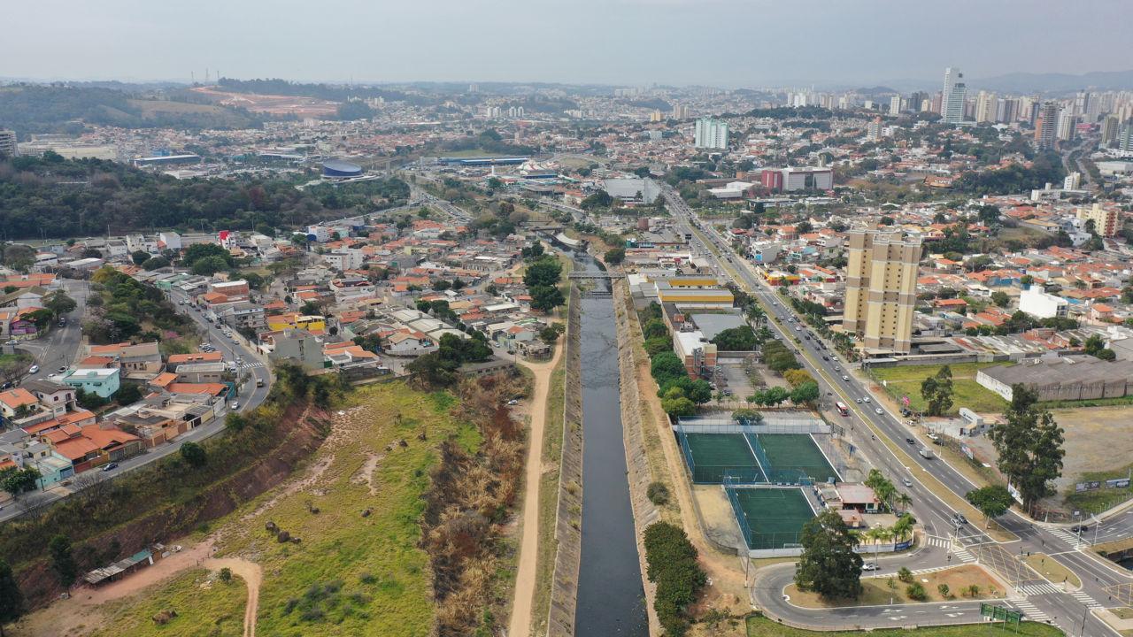 imagem aérea mostra rio no meio, com construções nas margens.