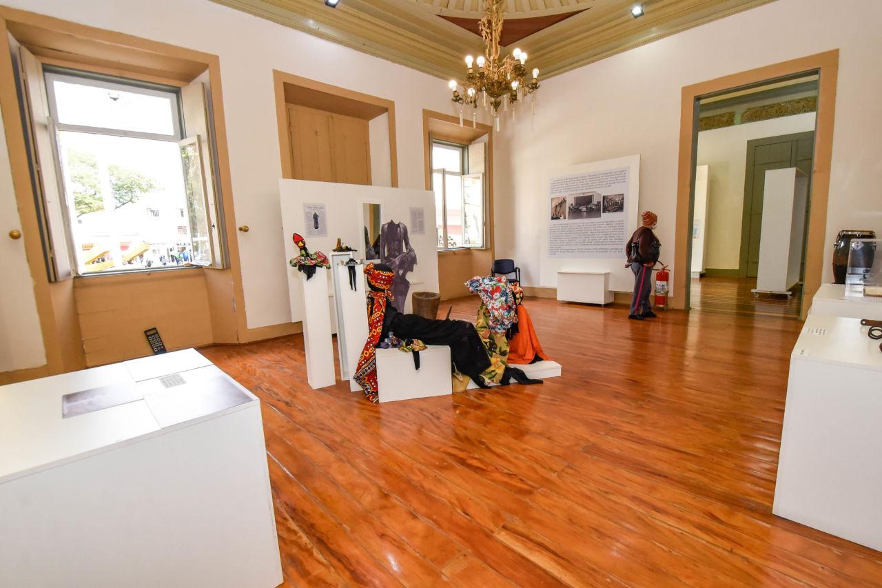 Sala de exposição, com piso de madeira, e estandes com objetos, e mulher de gorro ao fundo