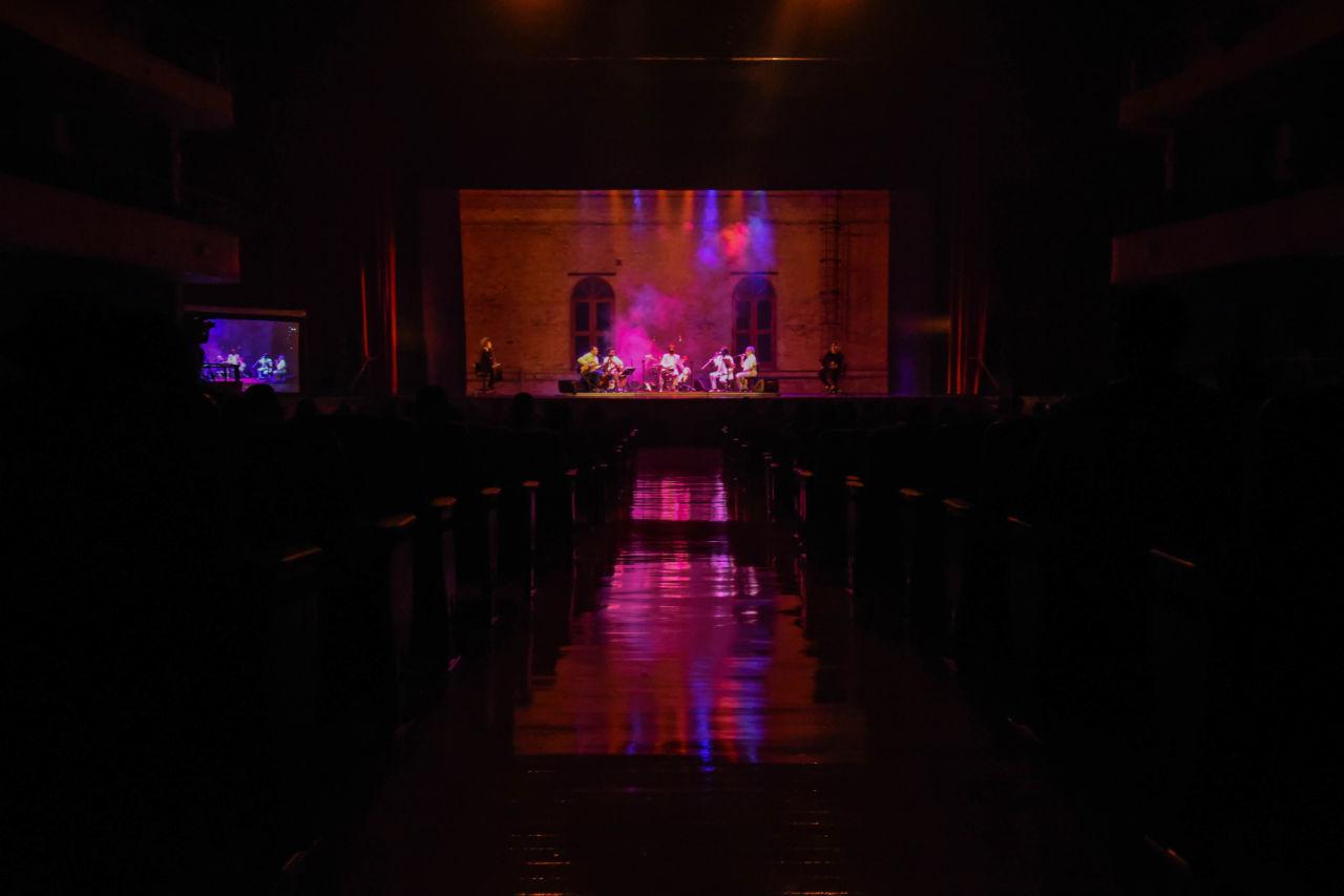 Teatro com luzes apagadas, com iluminação sobre palco com artistas de música e telão, com silhuetas do público na plateia