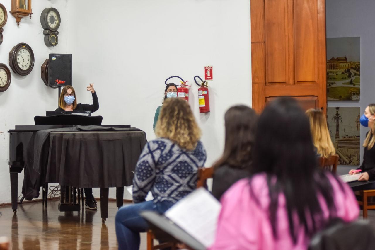 Mulher usando máscara e óculo, faz gesto levantando a mão esquerda, olhando para grupo de mulheres sentadas