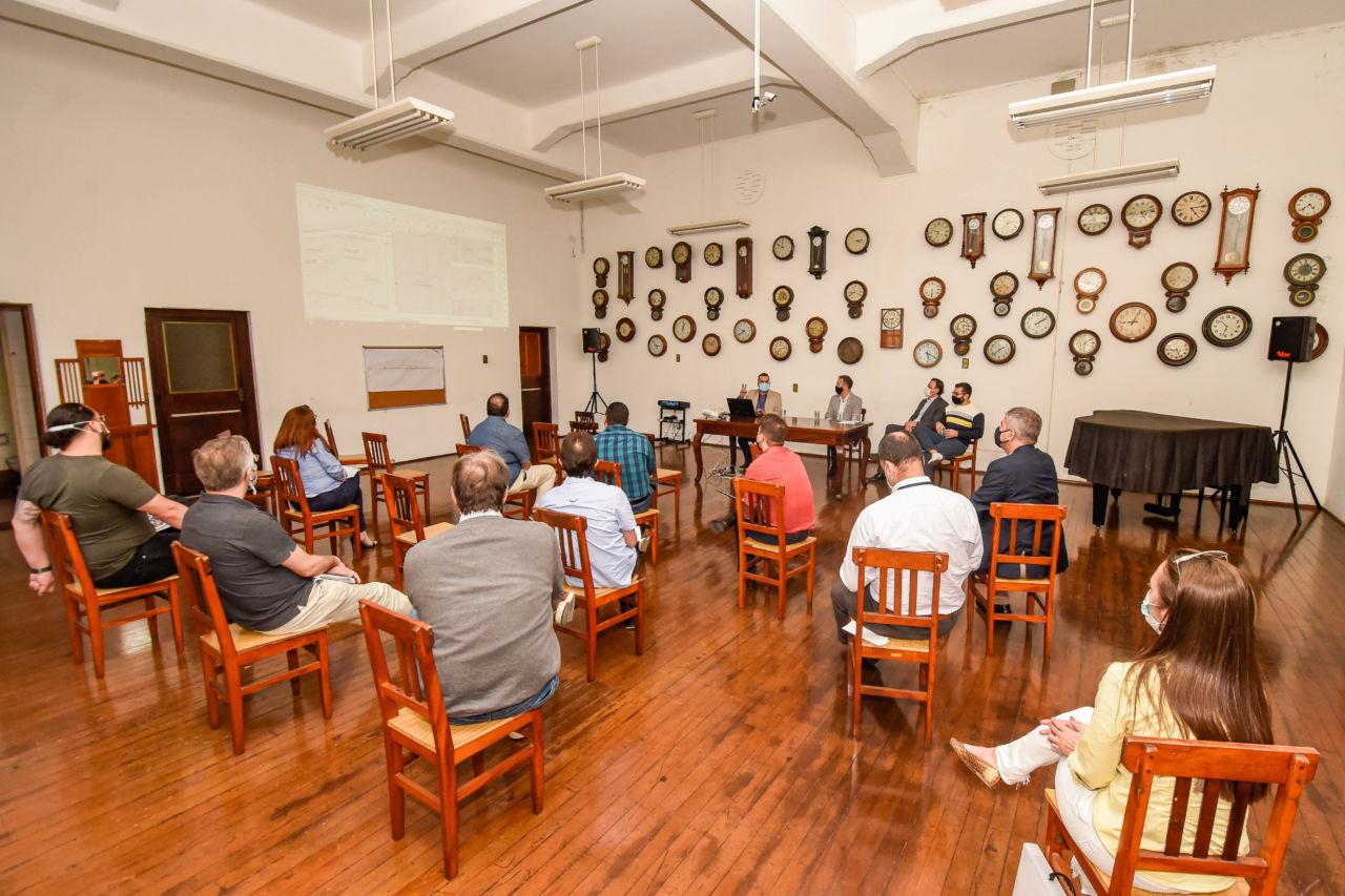 Foto de sala com pavimento de madeira e diversos relógios na parede, com pessoas de costas sentadas em mesas de madeira, olhando para parede lateral com projeção luminosa de apresentação, e quatro homens com máscaras, sentados de frente para a sala