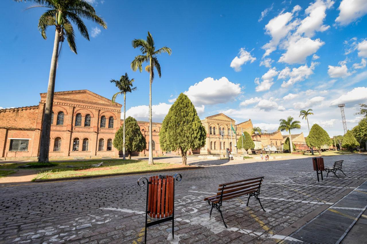 Praça com árvores e prédio histórico de tijolos à vista ao fundo, com bancos e lixeira de madeira no detalhe.