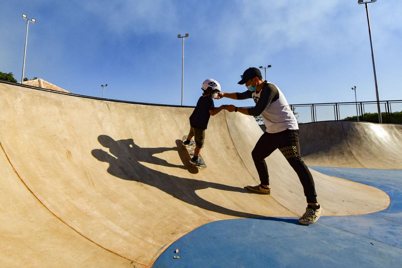Homem adulto de bonê e máscara auxilia criança de máscara e capacete em pista de skate