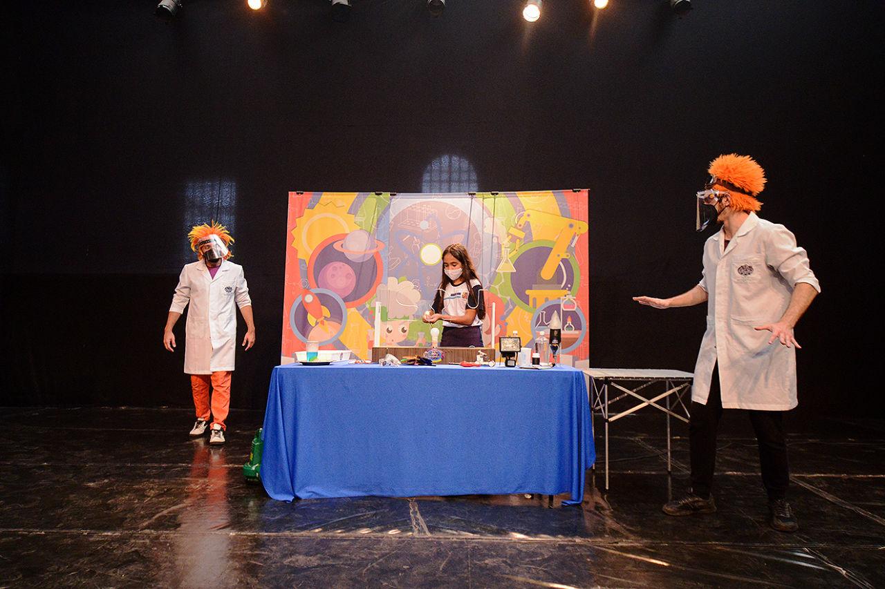 Em um palco escuro, há uma mesa no centro com toalha azul e diversos elementos. dois homens, que são atores, estão com perucas laranja. Atrás da mesa está uma garota de uniforma escolar, ela manipula um dos elementos da mesa.