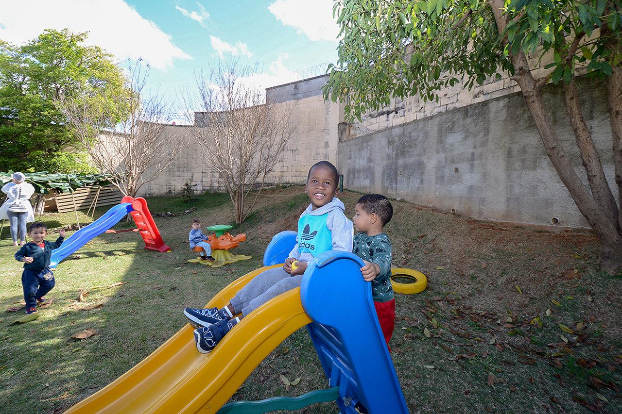 crianças brincam no escorregador, ao fundo parquinho infantil com crianças