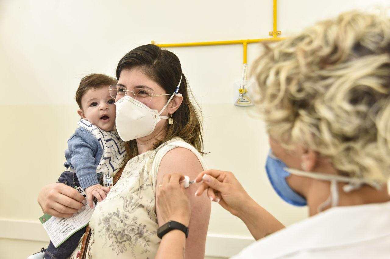 Mulher usando máscara e óculos recebe vacina no braço esquerdo, enquanto segura documento e criança com o braço direito