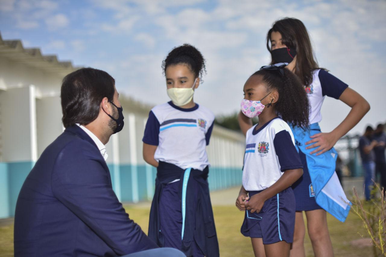 Homem moreno (o prefeito Luiz Fernando) está de terno azul, abaixado para conversar com três alunas,, são meninas que estão de  uniforme azul.