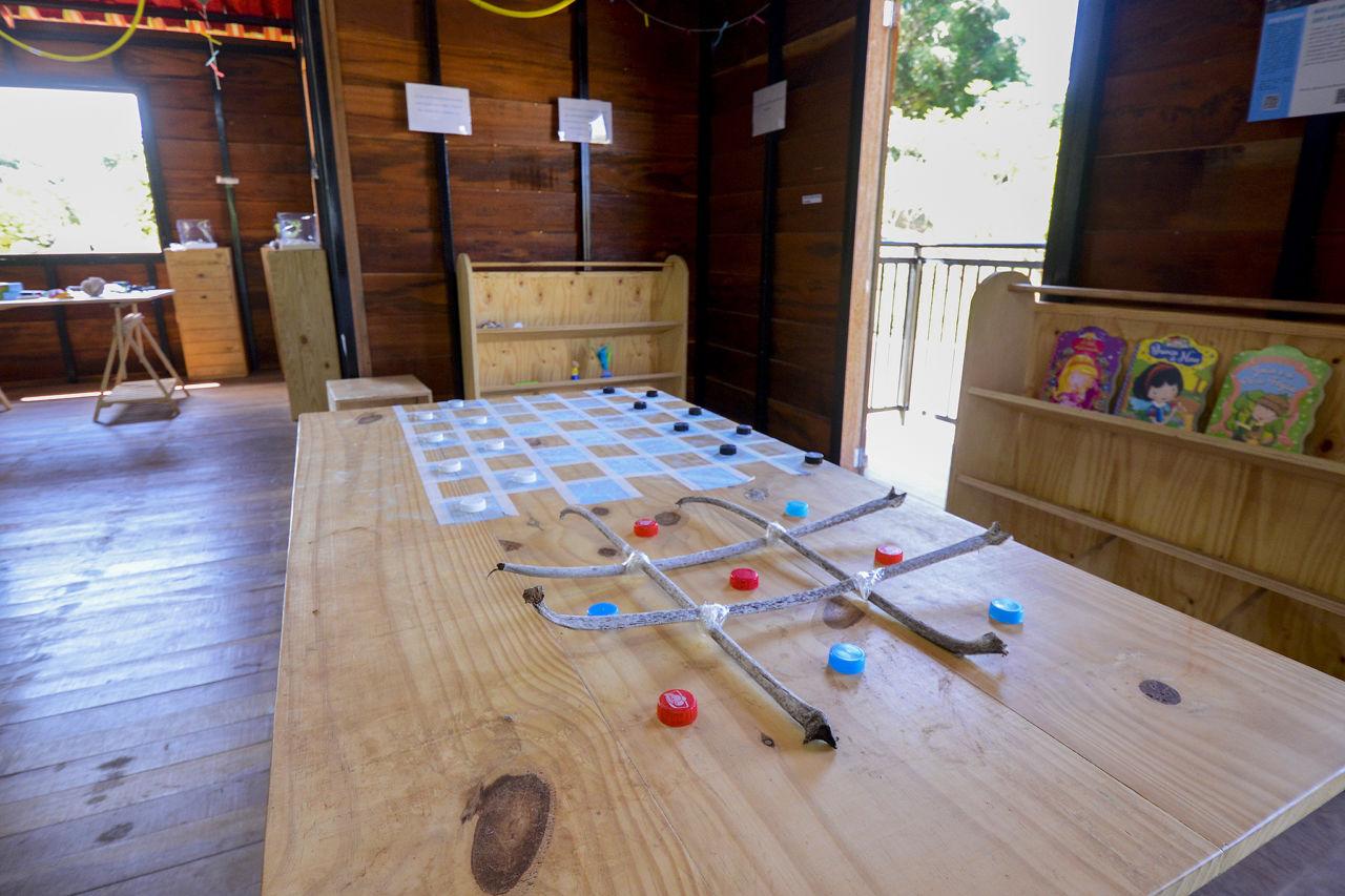 No foco está uma mesa de madeira clara, com jogo da velha feito com galhos e tampas de garrafas pet e xadrez pintado. No fundo há estantes da mesma madeira clara, com livros infantis.