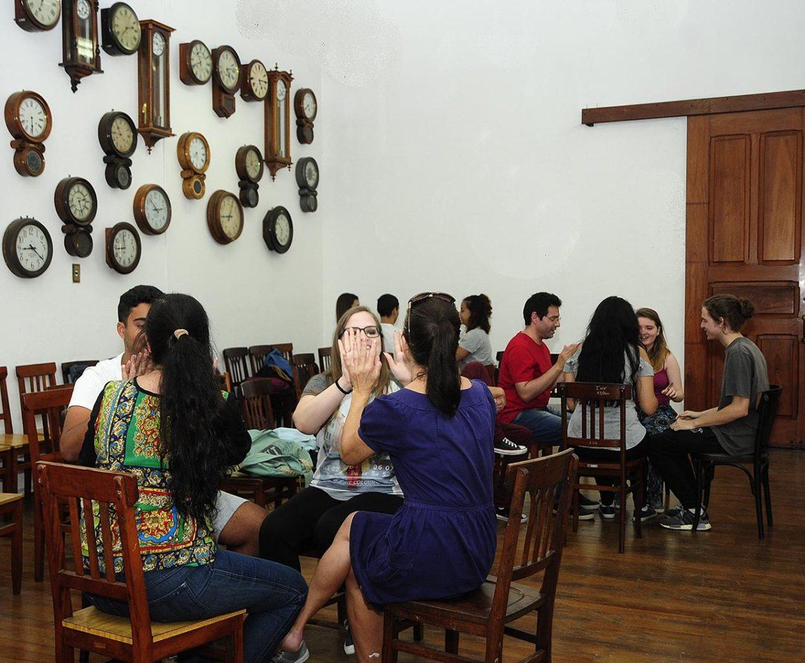 Três grupo de jovens sentados em cadeiras de madeira, em grupos de quatro pessoas, conversando e interagindo com as mãos, com relógios de diversos tamanhos e formatos ao fundo
